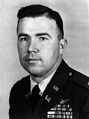 A black and white image of Bruce Crandall in his military dress uniform. He is facing the camera and turned slightly to the left