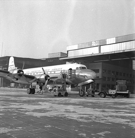A Pan Am Douglas DC-4 seen parked in front of a hangar at Berlin Tempelhof in January 1954. Bundesarchiv B 145 Bild-F001302-0004, Berlin, Flughafen Tempelhof.jpg