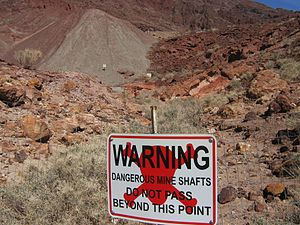 Mine safety - Warning sign near a dangerous area filled with open mineshafts, Calico Ghost Town, California.
