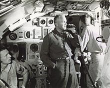 Submarine commanding officer using a microphone to address the ship's crew over the public address system in the submarine's control room with another officer facing away in background.