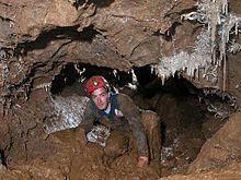 Um homem cedendo passagem enlameada com formações helictite nas paredes e teto