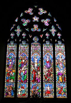 This stained glass window is divided into five long sections, above which the stone tracery looks like a lacey medallion. The colours are not like Medieval glass; there is a lot of bright red, pale blue, apple green, mauve and pink.