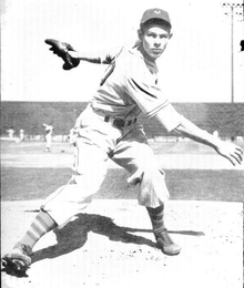 A man wearing a baseball uniform stands on the pitcher's mound having just thrown a baseball.