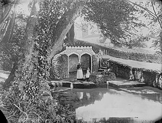 Country scene with a woman and girl by a well and a man-made pond.