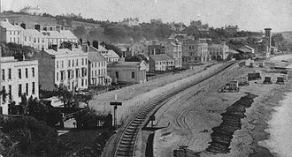 Dawlish railway station -  Dawlish in the 1870s with the station and chimney for the atmospheric pumping engine in the right background.