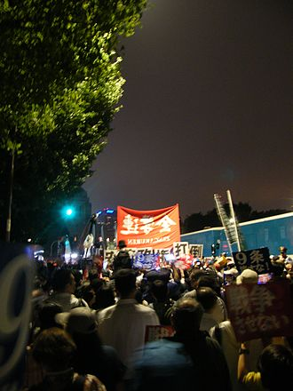 2015 Japanese military legislation - Demonstrators and police buses outside the Japanese National Diet on Friday September 18, 2015 during the debate in the House of Councillors shortly before the legislation was passed in the early hours of September 19th. A Zengakuren banner is visible in the middle of the image.