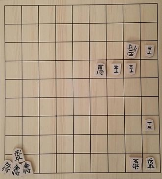 Shogi - Another popular style of shogi pieces different from the usual Japanese characters. Shows a 7-move tsumeshogi problem. White has pawns on 13, 24, 34; king on 23; and a promoted rook on 29. Black has a bishop on 44, a pawn on 17, a lance on 19, and a rook, two golds, and a silver in hand.