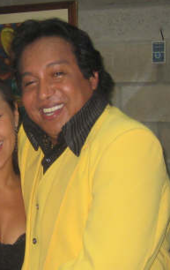 A man with a yellow sweater smiling.