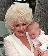 A woman with blonde curly hair holding a baby and smiling broadly