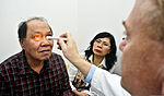 Dr. John Jarstad, right, with the Latter-day Saint Charities, checks the right eye of a cataract patient during a surgical civic action project aboard hospital ship USNS Mercy (T-AH 19) in North Sulawesi 120606-O-ZZ999-003.jpg