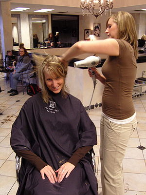 English: Woman in a salon drying another's blo...