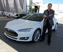 Musks stands, arms crossed and grinning, before a Tesla Model S