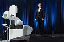 Musk standing next to bulky medical equipment on a stage