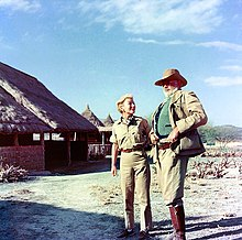 photograph of a man and woman with a brush covered hut in the background