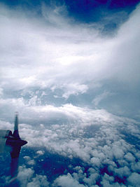 A photograph of the eye of a hurricane. One of the engines of a hurricane hunter aircraft can be seen in the bottom right portion of the image. Scattered clouds at the bottom give way to water. In the middle, the eyewall of the storm is clearly seen and near the top, there are wispy cirrus clouds. A portion of the top of the image shows the sky.