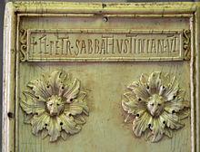 Photographie d'un morceau de marbre sculpté présentant un patronyme écrit en latin