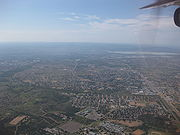 A broad view of the city facing east, the picture taken from a plane. In the middle is a large residential neighborhood. The downtown area and the Gaborone Dam are in the far right towards the horizon. At the bottom of the picture to the left is a large undeveloped area, and to the right is another neighborhood.