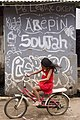Girl riding a bicycle with graffiti in the background; April 2012.jpg