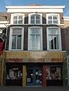 foto van Gepleisterde lijstgevel met gewijzigde pui. Huis met schilddak