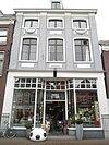 foto van Huis met gepleisterde pilastergevel met festoenen; pui modern, top verloren