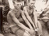 Two men without shirts on sit surrounded by soldiers