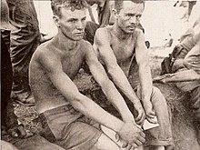 Twee mannen zonder shirts op te zitten, omringd door soldaten