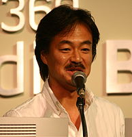 A 43-year-old Japanese man with neck-length black haired, speaking into a microphone and facing slightly to the camera's right.
