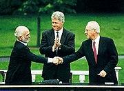 לחיצת יד בין חוסיין מלך ירדן ליצחק רבין, בנוכחות נשיא ארצות הברית קלינטון