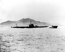 A World War II-era submarine in a body of water with a land mass in the background