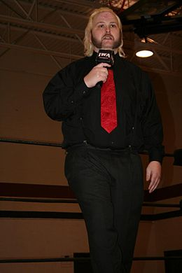 A male wrestler dressed casually in a wrestling ring holding a microphone