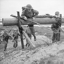 Two soldiers clamber over a wooded obstacle. Two more soldiers, in the background, run towards the obstacle.