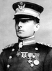 Head and shoulders of a white man standing erect, wearing a peaked cap over his eyes and a double-breasted military jacket with thick braided cords on the shoulders, three medals on the left breast, and a star-shaped medal hanging from his neck.