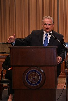 Clean-shaven man in his 60s, with gray hair, wearing glasses, dressed in a dark suit and blue tie, speaking from behind a dark, varnished wooden lectern, with his right arm outstretched.  The front of the lectern is emblazoned with the Great Seal of the United States.