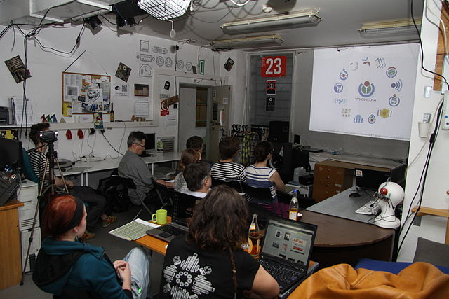 "Chmee2 talking about how Wikipedia works to students in Prague. The unique atmosphere of Brmlab proved to be a great place to interact with ""Wikipedians-to-be"""