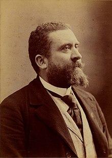 Fotografia monocromática de um homem barbudo, de perfil.