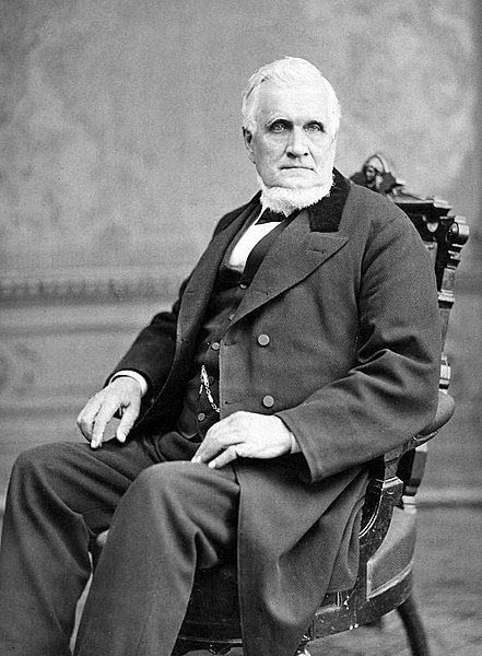File:John Taylor seated in chair.jpg