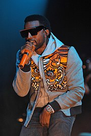A man wearing sunglasses, blue jeans, a gray sweatshirt and an orange vest with tiger-stripes designs performs on a stage into an orange microphone.