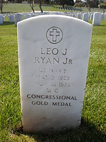 "A white-colored tombstone stands in the middle of a cemetery. ""Leo J. Ryan Jr"" is engraved on it."