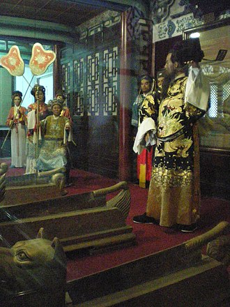 Sculptures inside the Lord Bao Memorial Temple, a tourist attraction in Kaifeng, Henan, China. In this scene, a fearless Bao Zheng takes off his official headwear to challenge the empress dowager, in order to execute the prince consort Chen Shimei. Lord Bao Memorial Temple.jpg