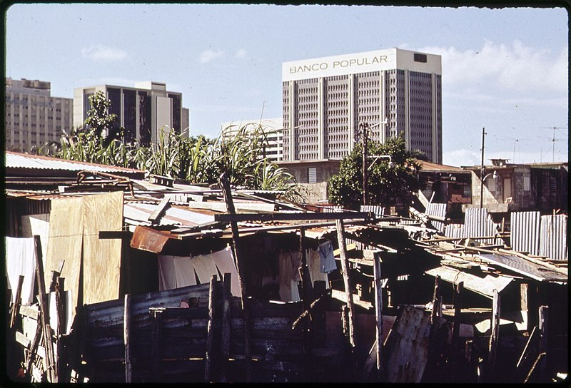 File:MODERN BUILDINGS TOWER OVER THE SHANTIES CROWDED ALONG THE MARTIN PENA CANAL - NARA - 546368.jpg