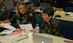 New Hampshire Wing Civil Air Patrol - First Lt. Cristal LePrade (left) of the Maine Wing's Bar Harbor Squadron and Capt. Sandy Riis of the New Hampshire Wing's Concord Composite Squadron look over mission reports.