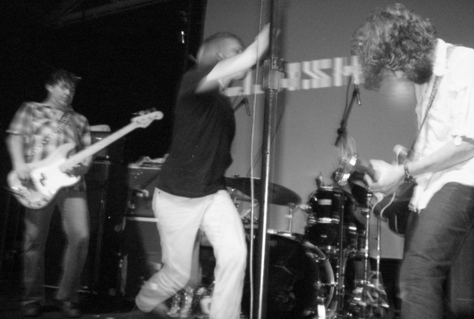 A photo of a rock band, Mudhoney, at a live show. The photo is blurred from the onstage motion. From left to right are the electric bassist, singer and guitarist.