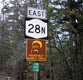 "Four signs are mounted on a pole. From top to bottom, they are: the word ""east"", a NY 28N shield, a yellow-on-brown sign with an outline of Theodore Roosevelt's face and the text ""Roosevelt-Marcy Trail"", and a reference marker for NY 28N."