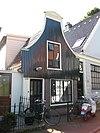foto van Houten huis met halsgevel (ingezwenkt voorschot) en bakstenen onderpui