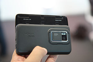 Nokia N900 - The 5-megapixel camera on the back of the Nokia N900. The hatch is open. The tilt stand is seen surrounding the camera.