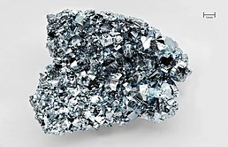 A silvery thumbnail-size chunk of osmium with a highly irregular crystalline surface.