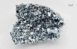 Arĝente brila bildikon-grandeca bloko de osmio kun tre neregula kristala surfaco.