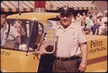 PARKING METER CHECKER STANDS BY HIS POLICE VEHICLE WHICH IS IMPRINTED WITH THE GERMAN WORD FOR POLICE (POLIZEI). IT... - NARA - 558137.tif