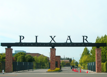 "In the foreground is a paved street leading to the gate's entrance. A sign reading ""PIXAR Animation Studios"" sits on top of stone columns in front of the gate that leads to several buildings."