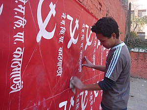 Nepal Workers Peasants Party - Installing posters for the Nepal Workers Peasants Party, at a hiti (public fountain) in Thamel